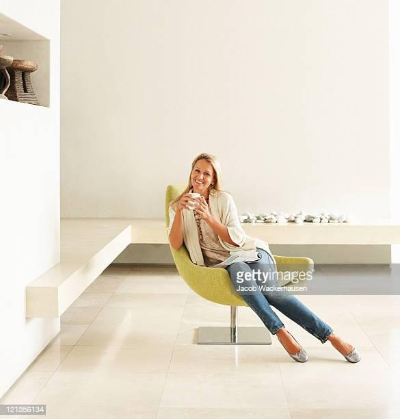 Relaxado mulher sorridente com copo de café em um quarto vazio