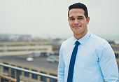 Smiling relaxed Hispanic businessman standing on a rooftop balcony overlooking an urban square, with copy space