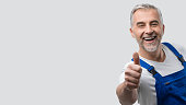 Smiling mature repairman and plumber giving a thumbs up and looking at camera