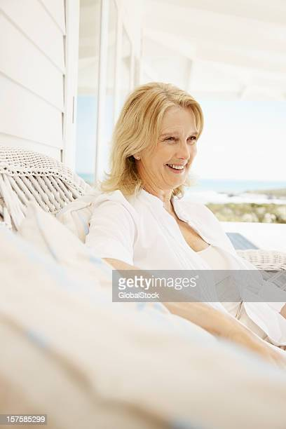 Smiling retired woman sitting on a couch at the porch