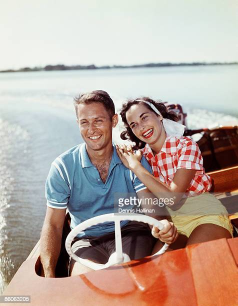 Smiling retro couple enjoying a speed boat ride