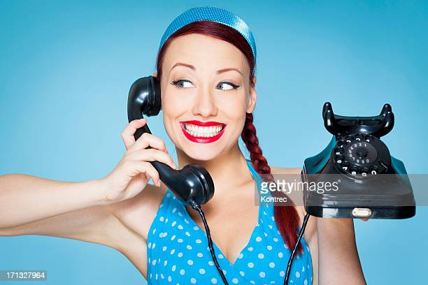 Smiling Retro woman with plaited hair holding old telephone