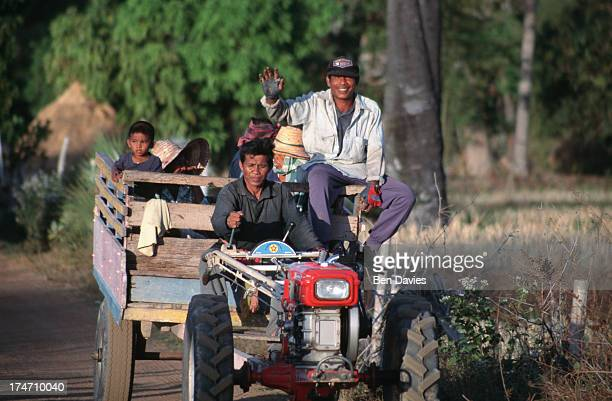 Smiling rice farmers drive home in a minitractor after harvesting the rice in Surin Province in Northeast Thailand Whilst in some parts of the...