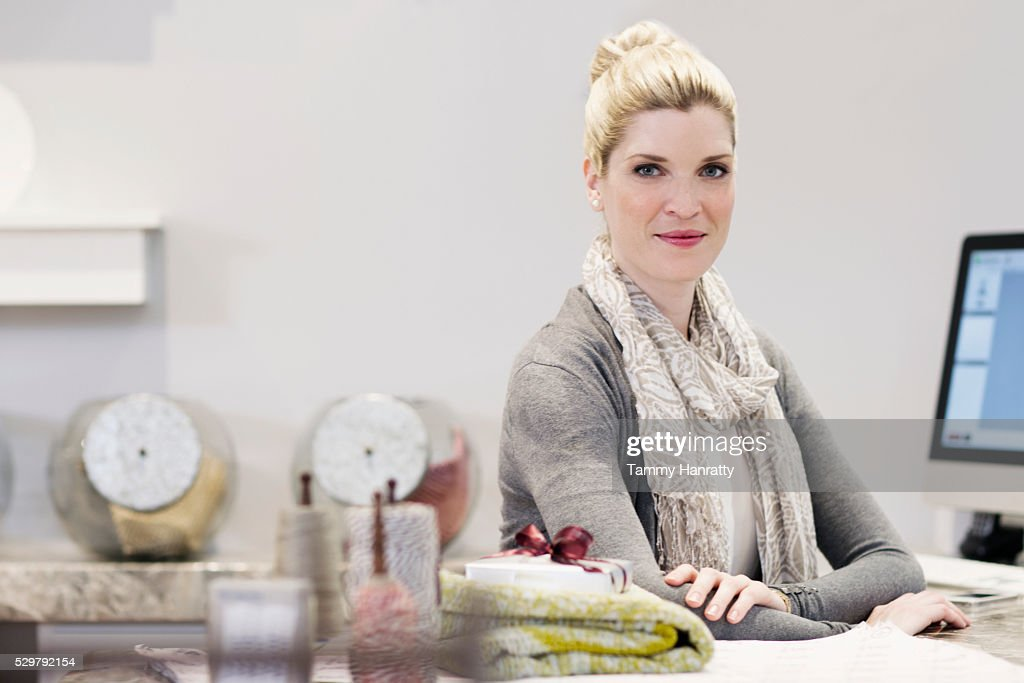 Smiling sales clerk behind counter : Stock Photo