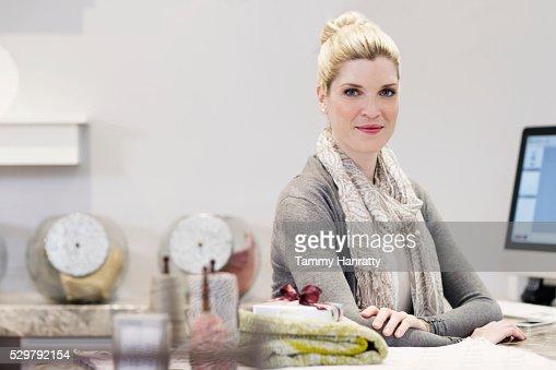Smiling sales clerk behind counter : Stock-Foto