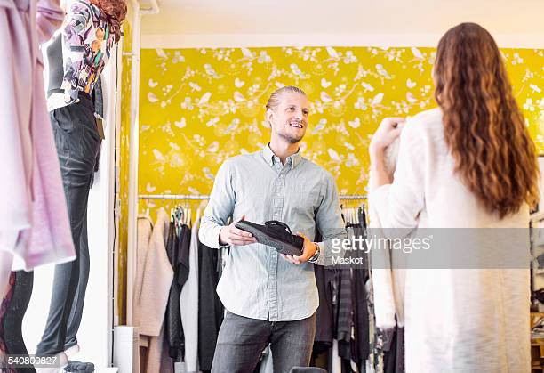 Smiling sales person looking at female customer in clothing store