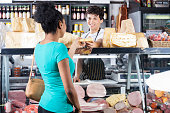 Smiling young salesman selling cheese to female customer at grocery shop