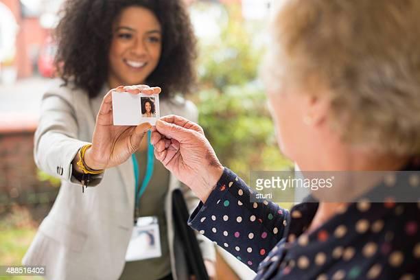 Lächelnd saleswoman präsentiert Ihre Karte vor der Tür.