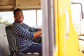 Smiling school bus driver sitting in bus