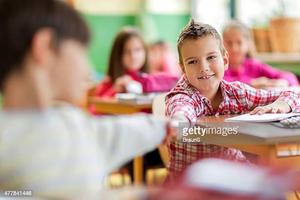 Écolier garçon souriant en passant des notes à son ami pendant un cours de danse.