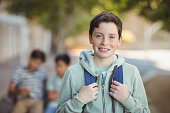 Portrait of smiling schoolboy standing with schoolbag in campus