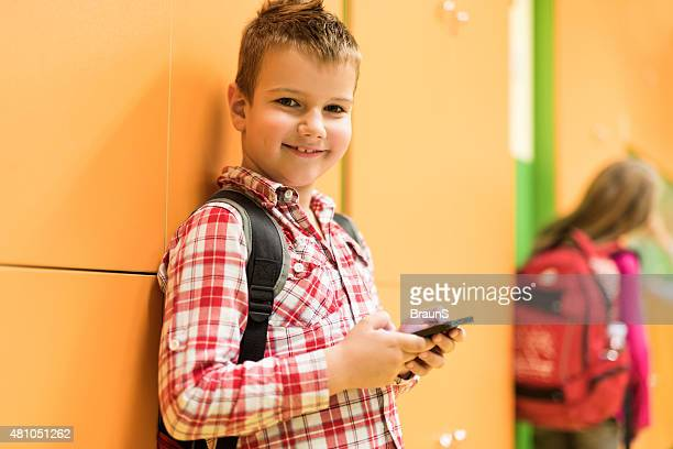 Lächelnd College-mit Handy in einer Schule Flur.
