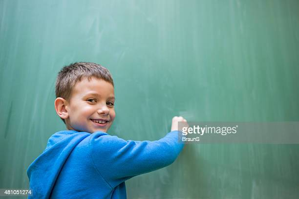 Smiling schoolboy writing on blackboard in the school.