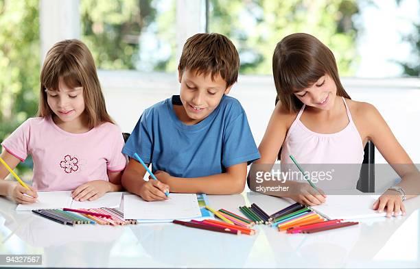 Smiling schoolchildren draws a picture.