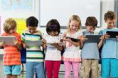 Smiling schoolchildren using digital tablets in classroom