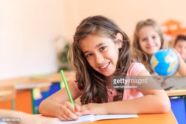 Écolière souriant dans la salle de classe de dessin