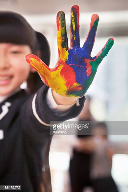 Smiling schoolgirl finger painting, close up on hand