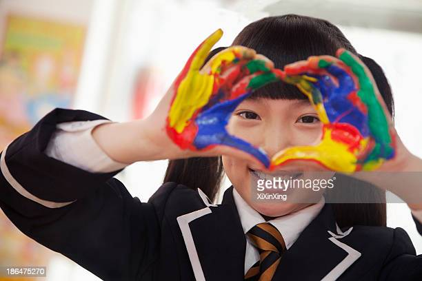 Smiling schoolgirl finger painting, close up on hands