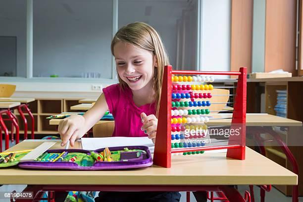 Smiling schoolgirl sitting at desk in her class