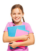 Charming young  schoolgirl holding exercise books in blue and pink covers isolated on white