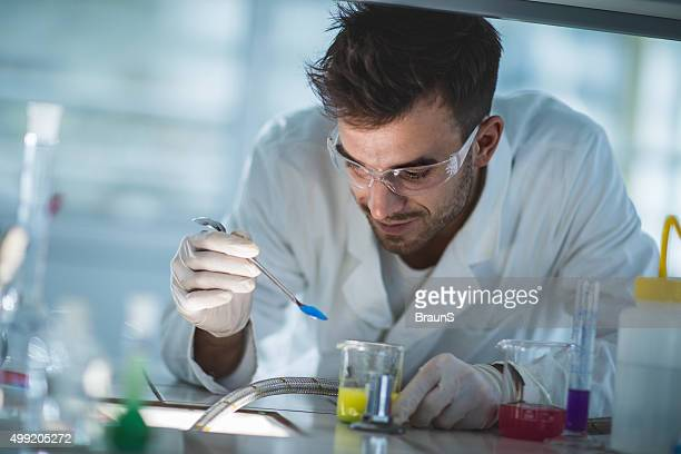 Smiling scientist examining chemical substances in a laboratory.