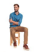 smiling seated young casual man looks to side on white background
