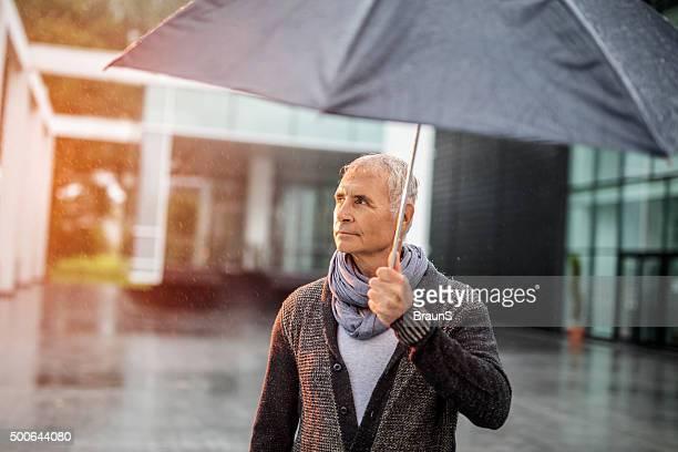 Smiling senior businessman with an umbrella during rainy day.