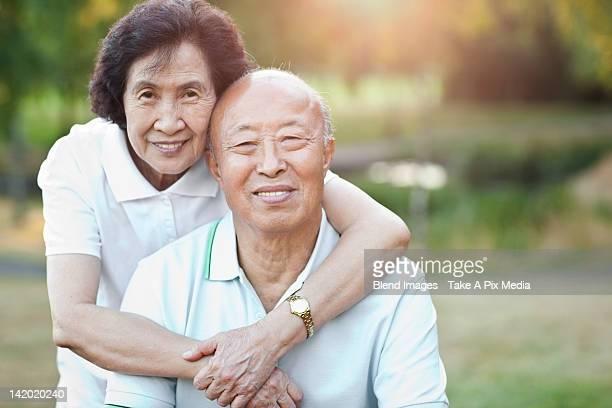 Smiling senior Chinese couple hugging