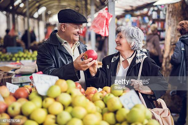Smiling senior couple buying fruit together at farmer's market.