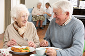 Senior Couple Enjoying Meal Together In Care Home