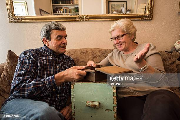 Smiling senior couple evoking their memories at home.