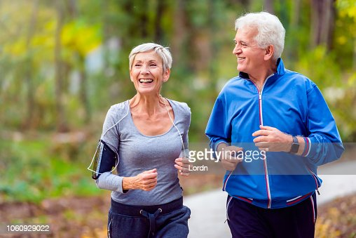 Smiling senior couple jogging in the park : Stock Photo