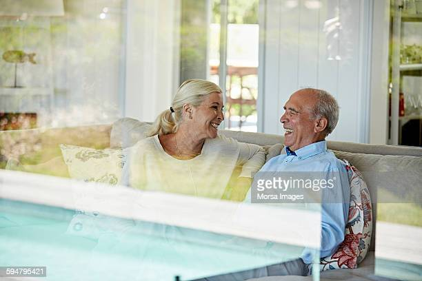 Smiling senior couple sitting on sofa