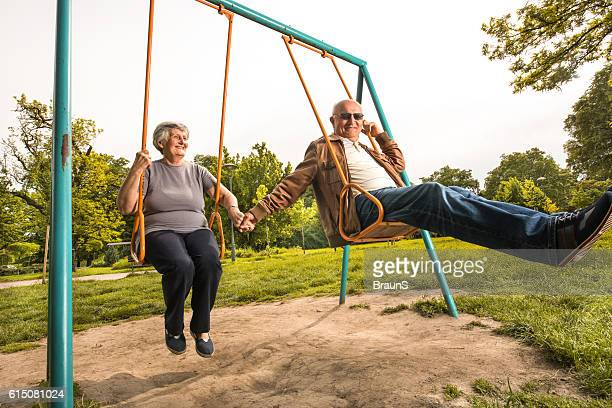 Smiling senior couple swinging together at the playground.