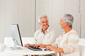 Smiling senior couple using computer at home