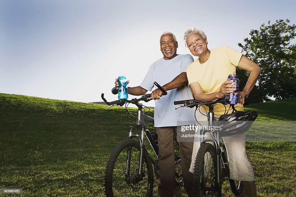 Smiling senior couple with mountain bikes : Stock Photo