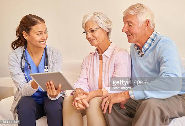 Smiling senior couple with their nurse during an appointment
