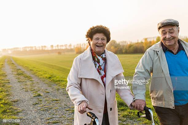 Smiling senior couple with wheeled walker in the nature