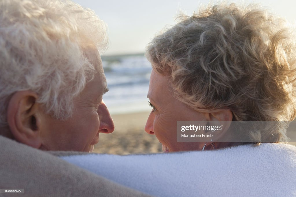 Smiling senior couple wrapped in towel on beach : Stock Photo