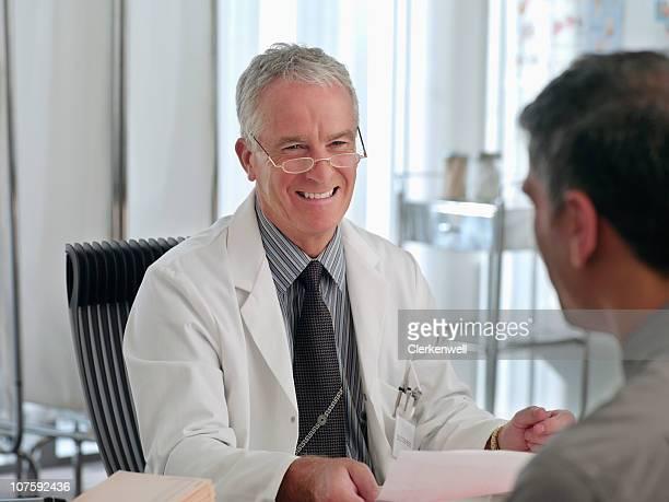 senior souriant médecin parlant avec son patient de l'hôpital
