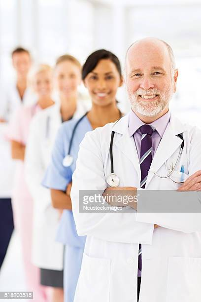 Smiling Senior Doctor With Row Of Medical Team