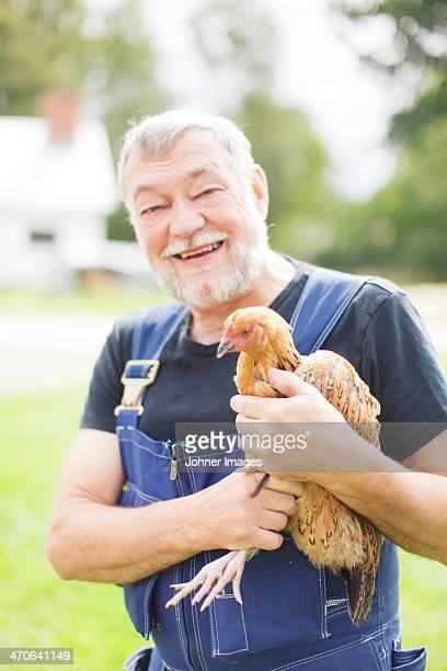 Smiling senior farmer holding chicken
