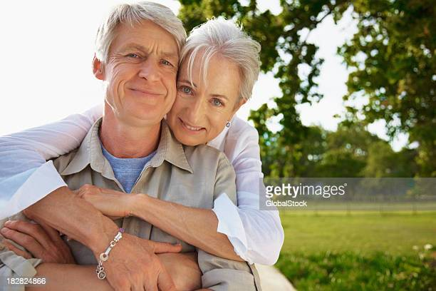 Smiling senior lady embracing her husband from behind