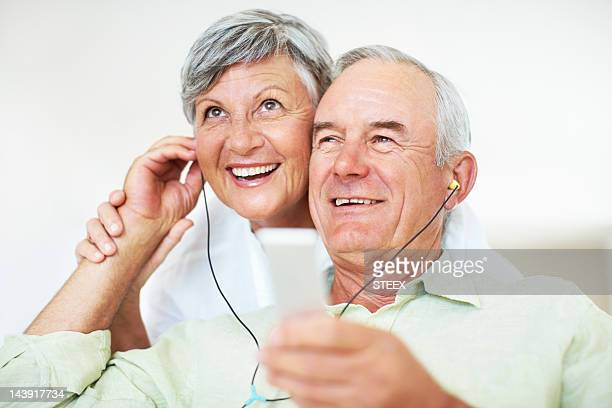 Smiling senior man and woman listening to music