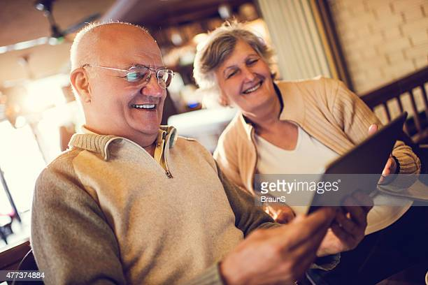 Smiling senior man and woman using digital tablet together.