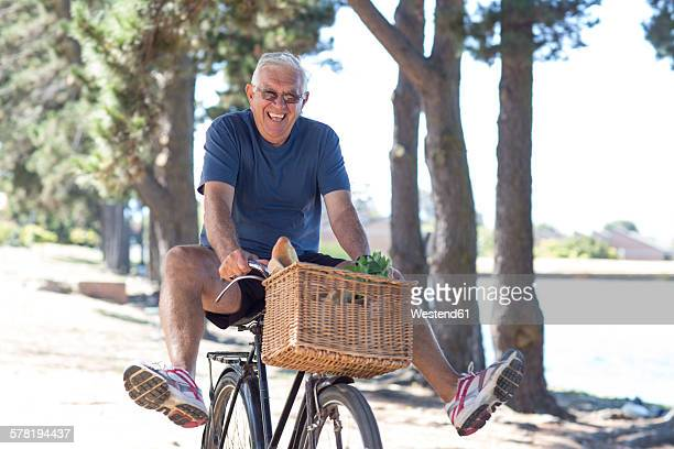 Smiling senior man balancing on bicycle
