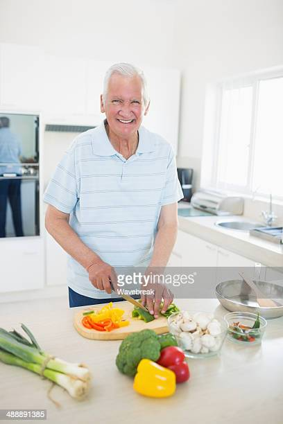 Smiling senior man chopping vegetables in kitchen