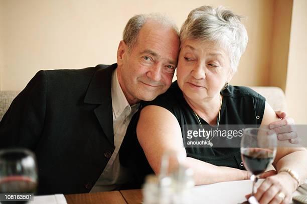 Smiling Senior Man Hugging Wife Drinking Wine at Restaurant Table
