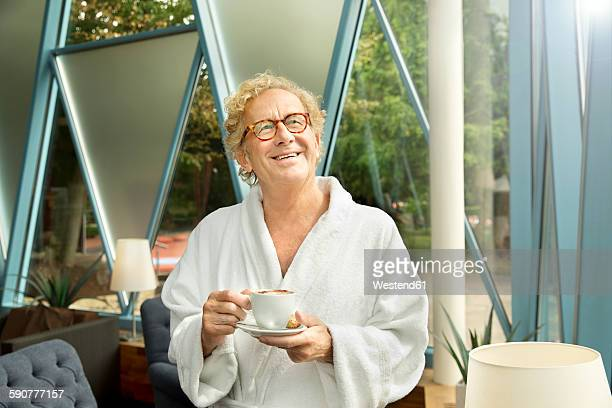 Smiling senior man in bathrobe with cup of coffee looking up