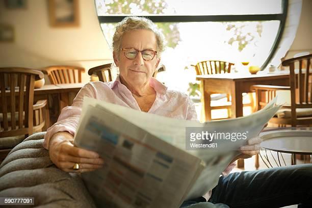 Smiling senior man in lounge room reading newspaper